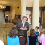 "Maine House ""#1 best"" tour guide Dan Fournier gives students the history lesson in the Hall of Flags"